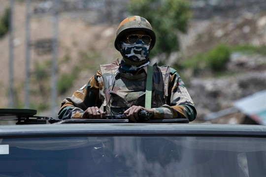 An Indian soldier atop a military vehicle as an army convoy moves on the Srinagar-Ladakh highway