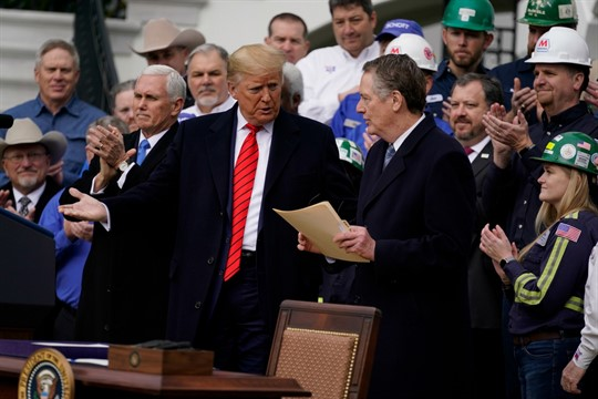 President Donald Trump speaks to U.S. Trade Representative Robert Lighthizer during a White House event.