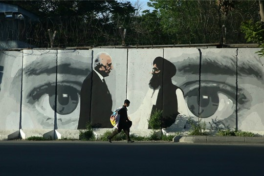 A young boy walks past a mural depicting American and Taliban negotiators, in Kabul
