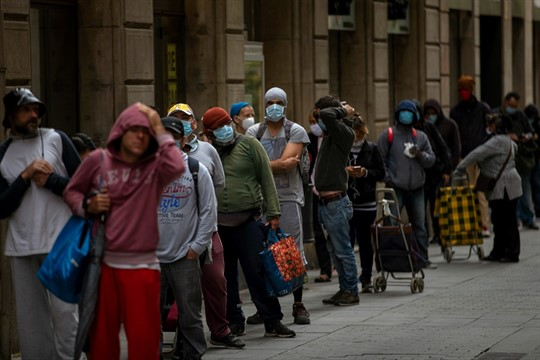 People line up as they wait to receive a ration of donated food in Barcelona