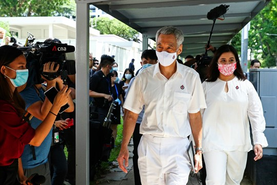 Prime Minister Lee Hsien Loong arrives at a nomination center with his team, in Singapore
