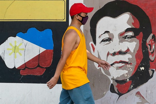 A man walks past an image of Philippine President Rodrigo Duterte in Manila, Philippines