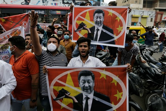 Protesters hold banners with the face of Chinese leader Xi Jinping during a demonstration against China