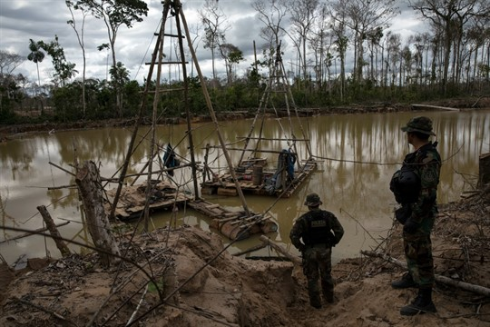 Police special forces stand next to illegal mining machinery in Peru's Tambopata province