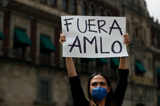 """A woman holds up a sign reading """"AMLO out"""" in Spanish during a protest, Mexico City"""