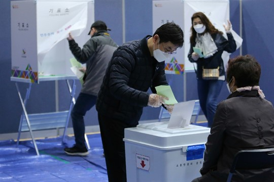 A man casts his vote for the parliamentary election at a polling station in Seoul