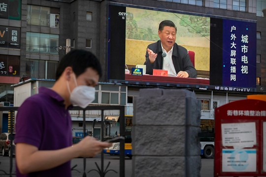 A man walks past a large video screen showing Chinese leader Xi Jinping speaking in Beijing