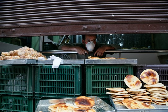 A Kashmiri man waits for customers during a nationwide lockdown to control the spread of coronavirus