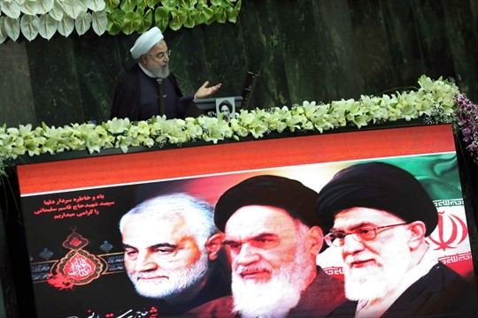 Iranian President Hassan Rouhani speaks behind a screen showing portraits of Iranian political figures