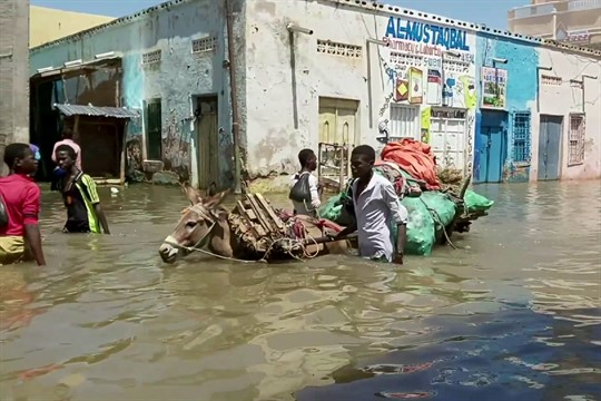 People wade through a flooded street in Beledweyne, central Somalia.
