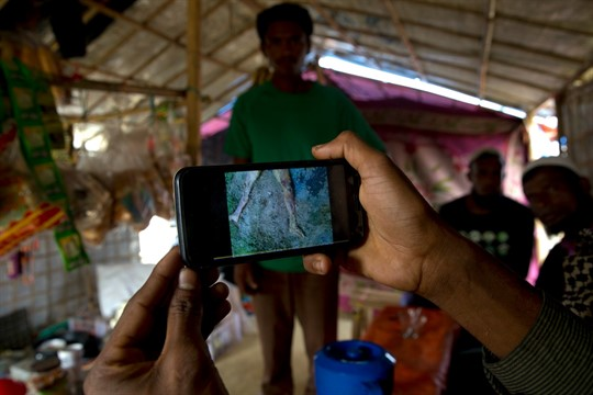 A Rohingya Muslim refugee in Bangladesh shows a mobile video of a massacre by Myanmar's military.