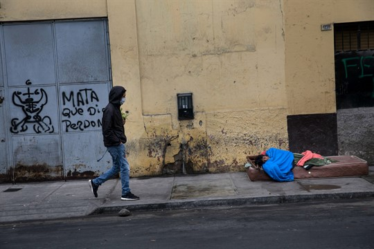 A man wearing a face mask walks near a homeless person in Lima, Peru