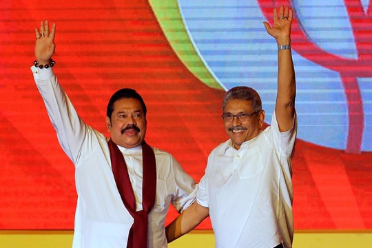 Sri Lankan President Gotabaya Rajapaksa and his brother, Prime Minister Mahinda Rajapaksa, wave at a convention