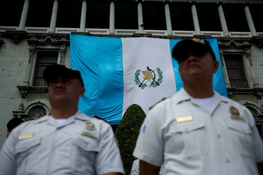 Police stand guard at the National Palace as protestors demonstrate against then-President Jimmy Morales and corruption