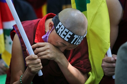 An exiled Tibetan cries during a march marking the 60th anniversary of the 1959 Tibetan uprising