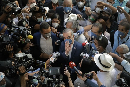 Luis Abinader, the president-elect of the Dominican Republic, is surrounded by journalists at a voting center.