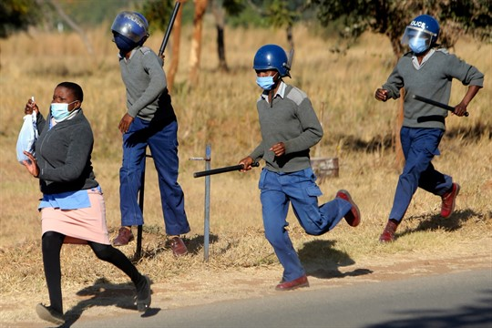 Riot police chase a nurse who was protesting at a government hospital in Harare