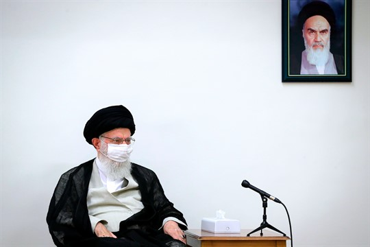 Iran's supreme leader, Ayatollah Ali Khamenei, sits under a portrait of the revolutionary founder, Ayatollah Khomeini.