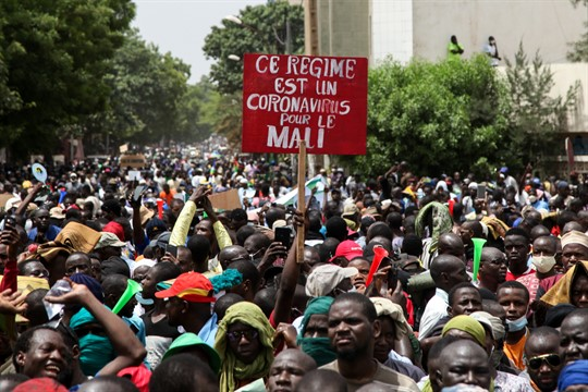 "Demonstrators hold a placard in French reading, ""This regime is a coronavirus for Mali,"" in Bamako."