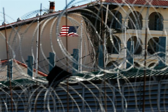 Seen through razor wire, a U.S. flag flies near the International Bridge 1 Las Americas