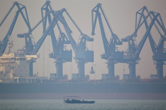 A fishing boat sails near the cranes of Cao Feidian Port in Tangshan, China.