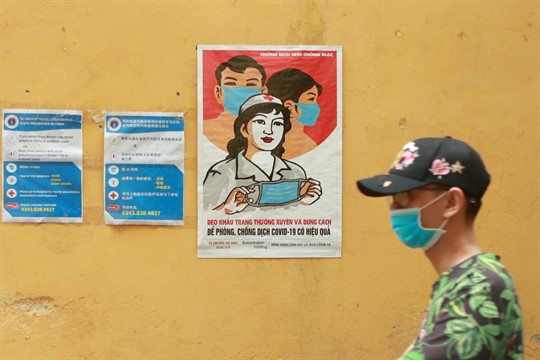 A man walks past a poster encouraging people to wear face masks correctly in Hanoi, Vietnam