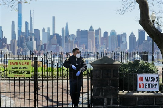 A security guard stands at a closed park with a view of the New York skyline