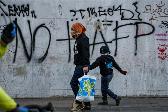 A man and a boy walk past graffiti against AFPs, Chile's pension system, in Santiago