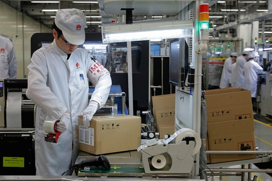 A staff member works on a mobile phone production line at a Huawei factory