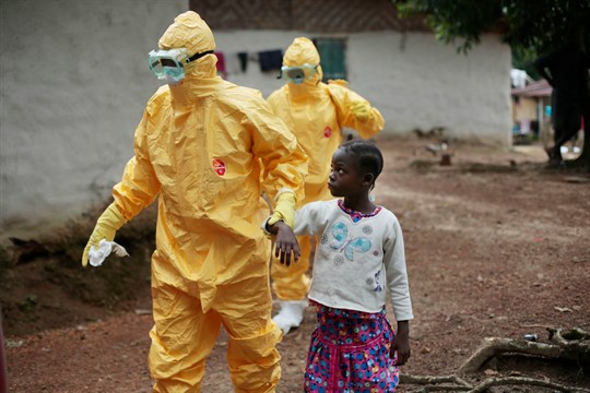 A young girl in Liberia is taken to an ambulance after showing signs of Ebola.