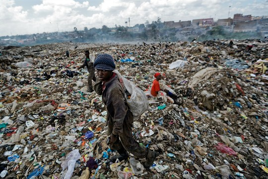 A man scavenges for pieces of plastic at a dump in the Dandora slum of Nairobi