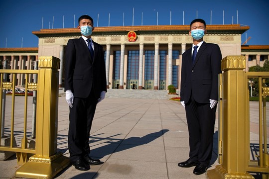 Security officials wearing masks stand guard outside the Great Hall of the People in Beijing