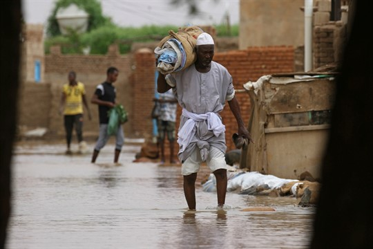 A man wades through a flooded road in the town of Shaqilab, Sudan