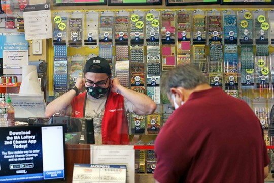 A clerk waits on a customer at a convenience store that sells lottery tickets in Mass.