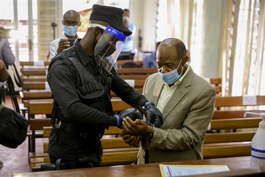 A policeman handcuffs Paul Rusesabagina before leading him out of court in Kigali, Rwanda