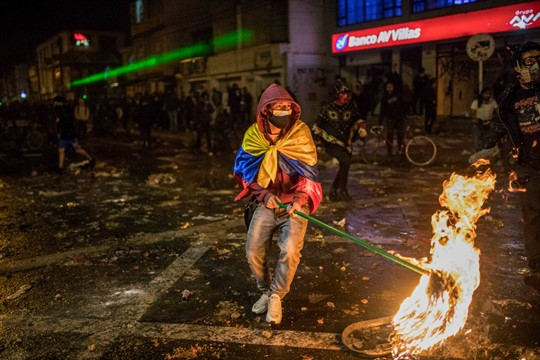 A demonstrator wields a burning mop during a clash with police in Bogota, Colombia.