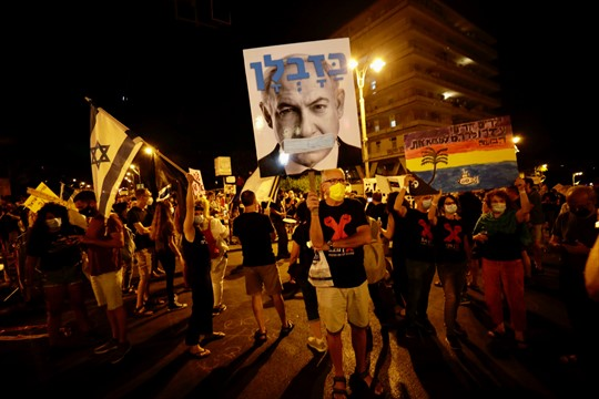 Israeli protesters hold signs and chant slogans during a demonstration against Prime Minister Benjamin Netanyahu.