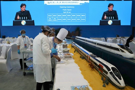 Chefs prepare a buffet as a live feed shows Prime Minister Imran Khan's speech in Beijing.