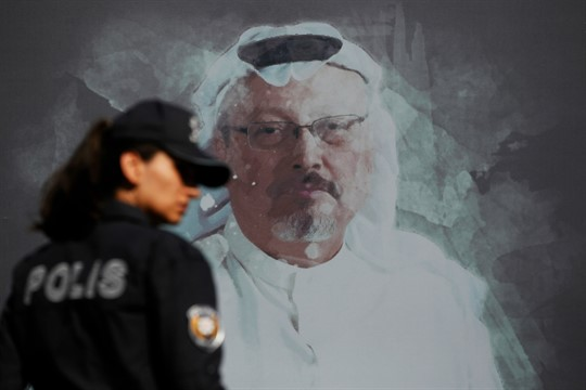 A police officer walks past a portrait of slain Saudi journalist Jamal Khashoggi, in Istanbul, Turkey.