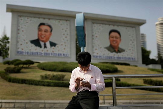 A man uses his smartphone in front of portraits of late North Korean leaders, in Pyongyang