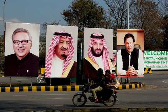 A motorcycle rides past portraits of Pakistani and Saudi leaders on display in Islamabad, Pakistan.