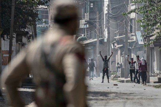 A police officer watches Kashmiri men protest following a shootout between police and militants, Srinagar