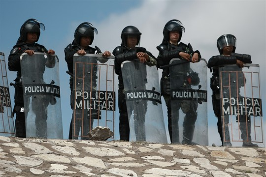 Mexican National Guard troops equipped with riot gear stand guard at Las Pilas dam, Camargo, Mexico