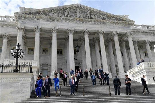 Members of the House of Representatives walk down the steps of Capitol Hill