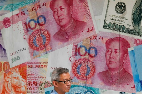 A man walks by a money exchange shop decorated with Chinese yuan banknotes