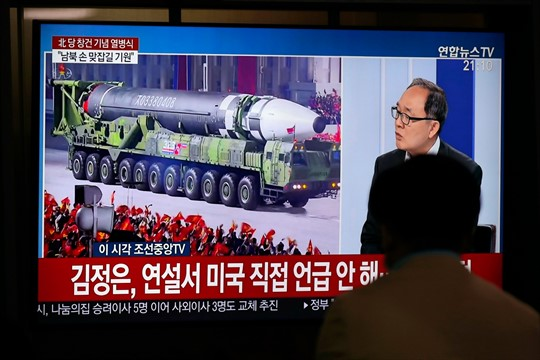 A TV screen shows a news program with an image of North Korea's new ballistic missile.