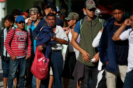 Honduran migrants wait for water during the trip north in hopes of reaching the U.S.