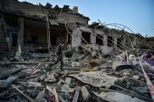 A soldier walks among debris from destroyed house in Ganja, Azerbaijan.