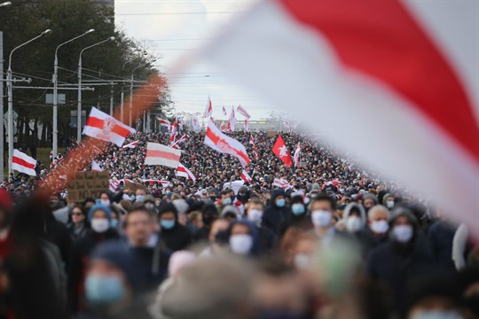People with old Belarusian national flags protest the official presidential election results in Minsk, Belarus