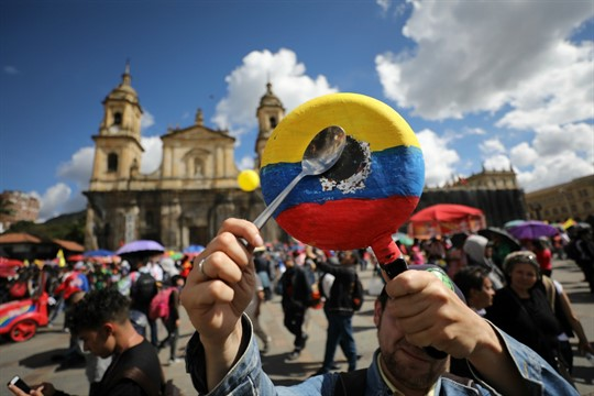An anti-government demonstrator bangs on a pan with the Colombian national colors during a strike